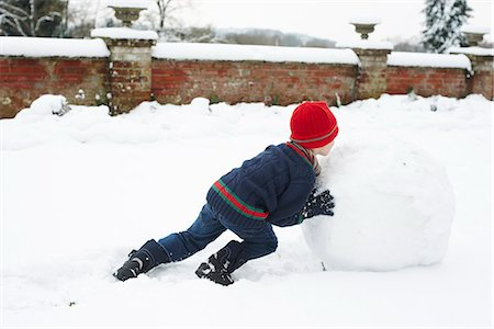 roll (people and animals rolling around) - Boy making snowman outdoors Stock Photo - Premium Royalty-Free, Code: 6113-06753361