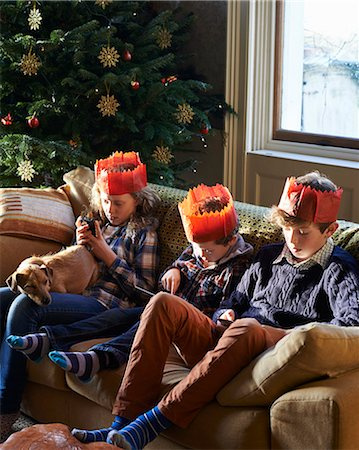 Children in paper crowns relaxing on sofa Stock Photo - Premium Royalty-Free, Code: 6113-06753376