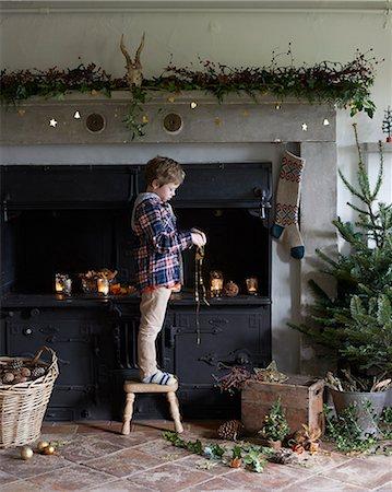 pantyhose kid - Boy decorating Christmas fireplace Stock Photo - Premium Royalty-Free, Code: 6113-06753378