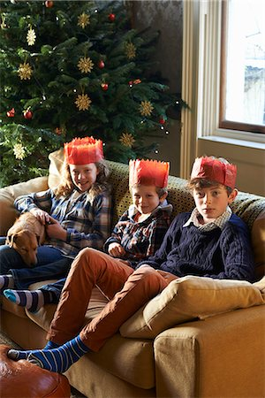 Children in paper crowns sitting on sofa Stock Photo - Premium Royalty-Free, Code: 6113-06753391