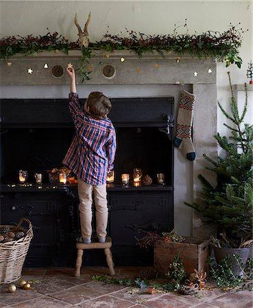 pantyhose kid - Boy decorating Christmas fireplace Stock Photo - Premium Royalty-Free, Code: 6113-06753400