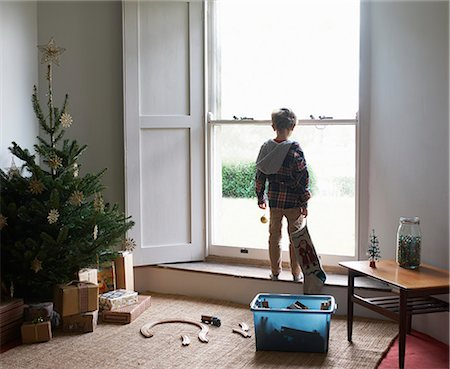 pantyhose kid - Boy holding Christmas stocking at window Stock Photo - Premium Royalty-Free, Code: 6113-06753402