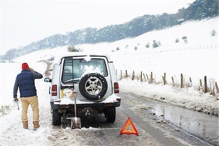 Man working on broken down car in snow Stock Photo - Premium Royalty-Free, Code: 6113-06753407