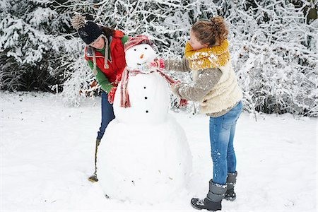 Mother and daughter making snowman Stock Photo - Premium Royalty-Free, Code: 6113-06753409