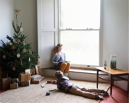 Children relaxing by Christmas tree Stock Photo - Premium Royalty-Free, Code: 6113-06753410