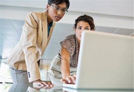 Businesswomen using laptop together Stock Photo - Premium Royalty-Free, Code: 6113-06753420
