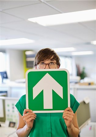 person holding sign - Businesswoman holding arrow sign in office Stock Photo - Premium Royalty-Free, Code: 6113-06753553