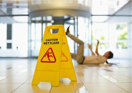Businessman slipping on wet office floor Stock Photo - Premium Royalty-Free, Code: 6113-06753567