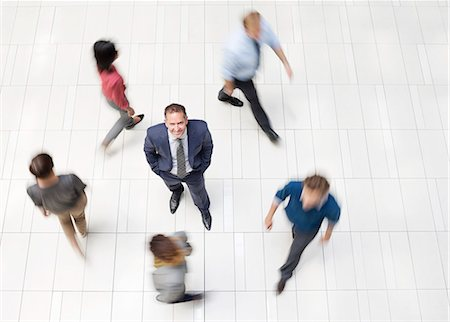 Businessman standing in busy office hallway Stock Photo - Premium Royalty-Free, Code: 6113-06753577