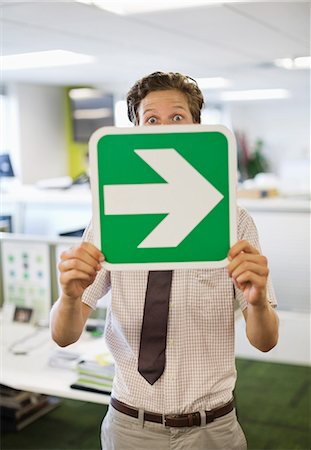 right - Businessman holding arrow sign in office Stock Photo - Premium Royalty-Free, Code: 6113-06753578