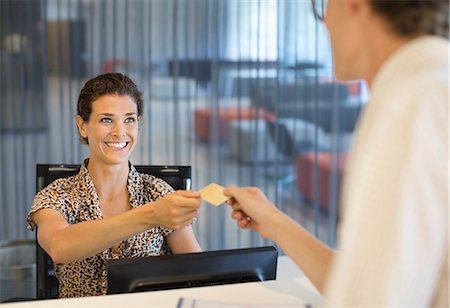 Businesswoman handing credit card to co-worker Stock Photo - Premium Royalty-Free, Code: 6113-06753581