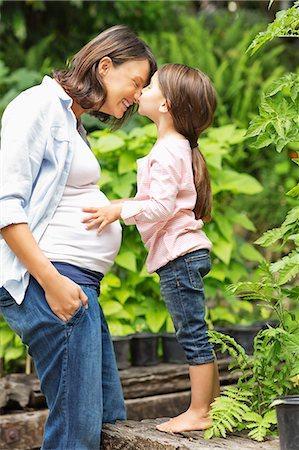 Girl kissing pregnant mother outdoors Stock Photo - Premium Royalty-Free, Code: 6113-06753644