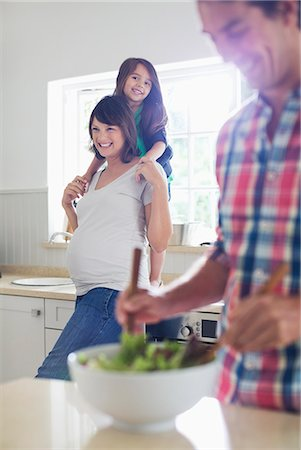 portrait of pregnant woman - Pregnant mother and daughter watching father toss salad Stock Photo - Premium Royalty-Free, Code: 6113-06753637