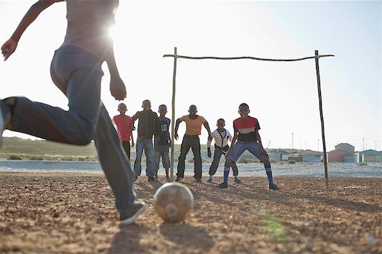 Boys playing soccer together in dirt field Stock Photo - Premium Royalty-Free, Image code: 6113-06753761