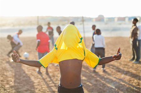 footballeur - Boy celebrating with soccer jersey on his head in dirt field Stock Photo - Premium Royalty-Free, Code: 6113-06753765
