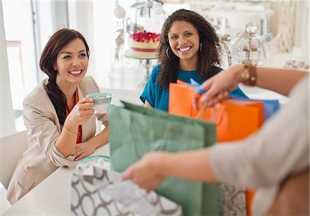 Woman showing friends shopping bags Stock Photo - Premium Royalty-Free, Code: 6113-06753737