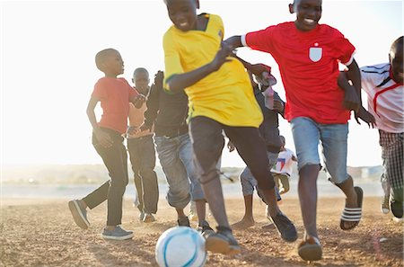 Boys playing soccer together in dirt field Stock Photo - Premium Royalty-Free, Code: 6113-06753811