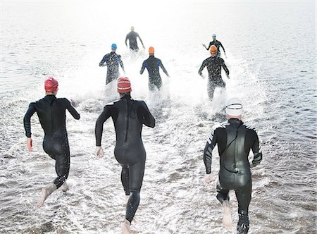 swimming - Triathletes in wetsuits running into ocean Stock Photo - Premium Royalty-Free, Code: 6113-06753966