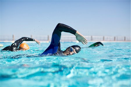 swimming - Triathletes in wetsuits racing in pool Stock Photo - Premium Royalty-Free, Code: 6113-06754067
