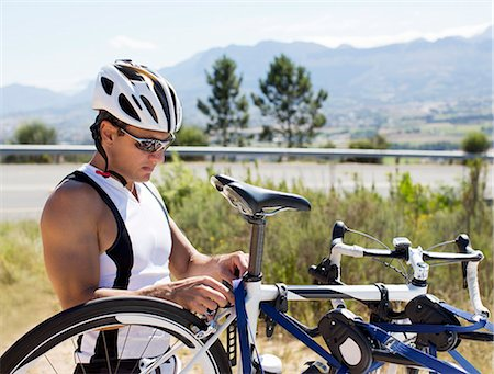 Man adjusting bicycle outdoors Stock Photo - Premium Royalty-Free, Code: 6113-06754077