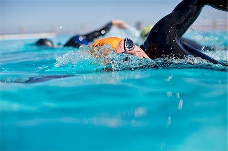 swimming pool water - Triathletes in wetsuit splashing in pool Stock Photo - Premium Royalty-Free, Code: 6113-06754098