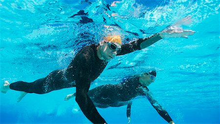 swimming - Triathletes in wetsuits underwater Stock Photo - Premium Royalty-Free, Code: 6113-06754030