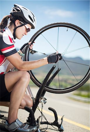 Cyclist adjusting tire on rural road Stock Photo - Premium Royalty-Free, Code: 6113-06754158
