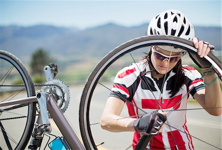 Cyclist adjusting tire on rural road Stock Photo - Premium Royalty-Free, Code: 6113-06754162