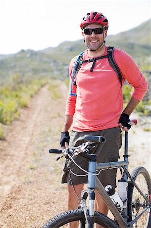 mountain biker smiling on dirt path Stock Photo - Premium Royalty-Free, Code: 6113-06754139
