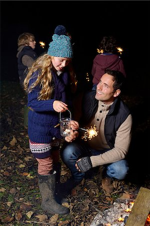 Father and daughter playing with sparkler Stock Photo - Premium Royalty-Free, Code: 6113-06720245