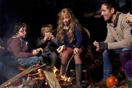 Family eating around campfire at night Stock Photo - Premium Royalty-Free, Code: 6113-06720249