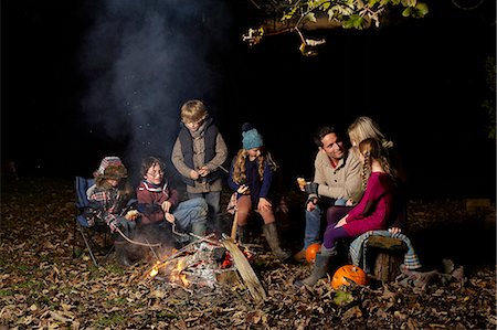 Family eating around campfire at night Stock Photo - Premium Royalty-Free, Code: 6113-06720251