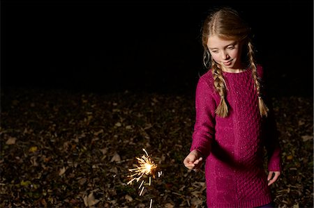 spark - Girl playing with sparkler outdoors Stock Photo - Premium Royalty-Free, Code: 6113-06720263