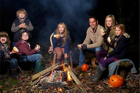 Family eating around campfire at night Stock Photo - Premium Royalty-Free, Code: 6113-06720231