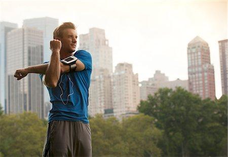 Runner stretching in urban park Stock Photo - Premium Royalty-Free, Code: 6113-06720372