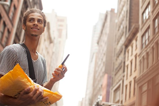 Man carrying mail on city street Stock Photo - Premium Royalty-Free, Image code: 6113-06720380