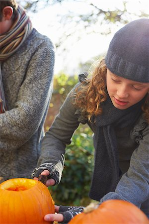 Children carving pumpkins together outdoors Stock Photo - Premium Royalty-Free, Code: 6113-06720310