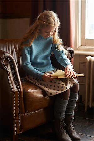 Girl reading book in armchair Stock Photo - Premium Royalty-Free, Code: 6113-06720323