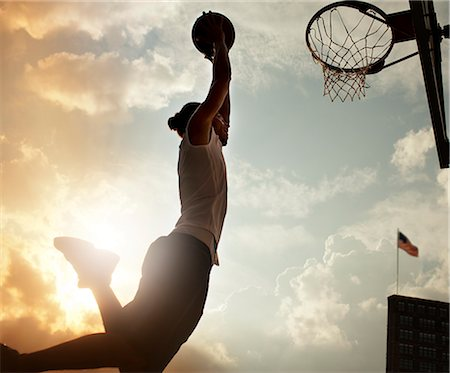 scoring - Man dunking basketball on court Stock Photo - Premium Royalty-Free, Code: 6113-06720334