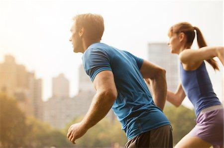 Couple running in urban park Stock Photo - Premium Royalty-Free, Code: 6113-06720339