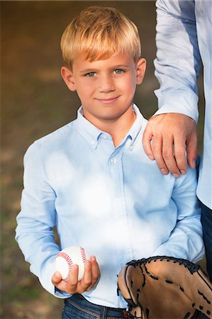 Boy holding baseball and glove with father Stock Photo - Premium Royalty-Free, Code: 6113-06720482