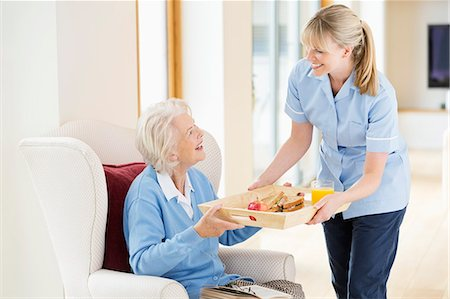 Caregiver giving older woman tray of food Stock Photo - Premium Royalty-Free, Code: 6113-06720661