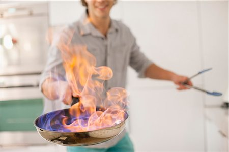 Man cooking with fire in kitchen Stock Photo - Premium Royalty-Free, Code: 6113-06720694