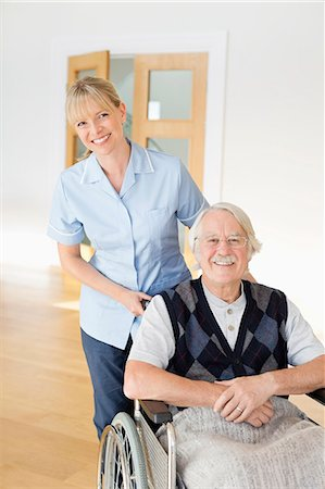 Caregiver pushing older man in wheelchair Stock Photo - Premium Royalty-Free, Code: 6113-06720611