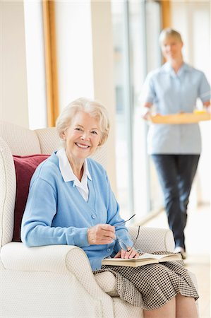 Older woman smiling in armchair Stock Photo - Premium Royalty-Free, Code: 6113-06720639