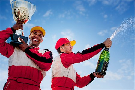 Racers holding trophy and champagne Stock Photo - Premium Royalty-Free, Code: 6113-06720779
