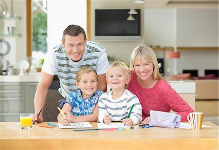 sister - Family smiling together at table Stock Photo - Premium Royalty-Free, Code: 6113-06720701