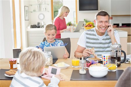 Family using technology at breakfast Stock Photo - Premium Royalty-Free, Code: 6113-06720708