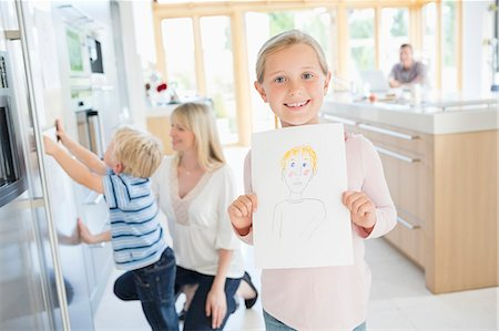 fridge - Girl showing off drawing in kitchen Stock Photo - Premium Royalty-Free, Code: 6113-06720723