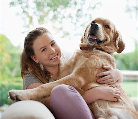 Smiling girl hugging dog on sofa Stock Photo - Premium Royalty-Free, Code: 6113-06720860
